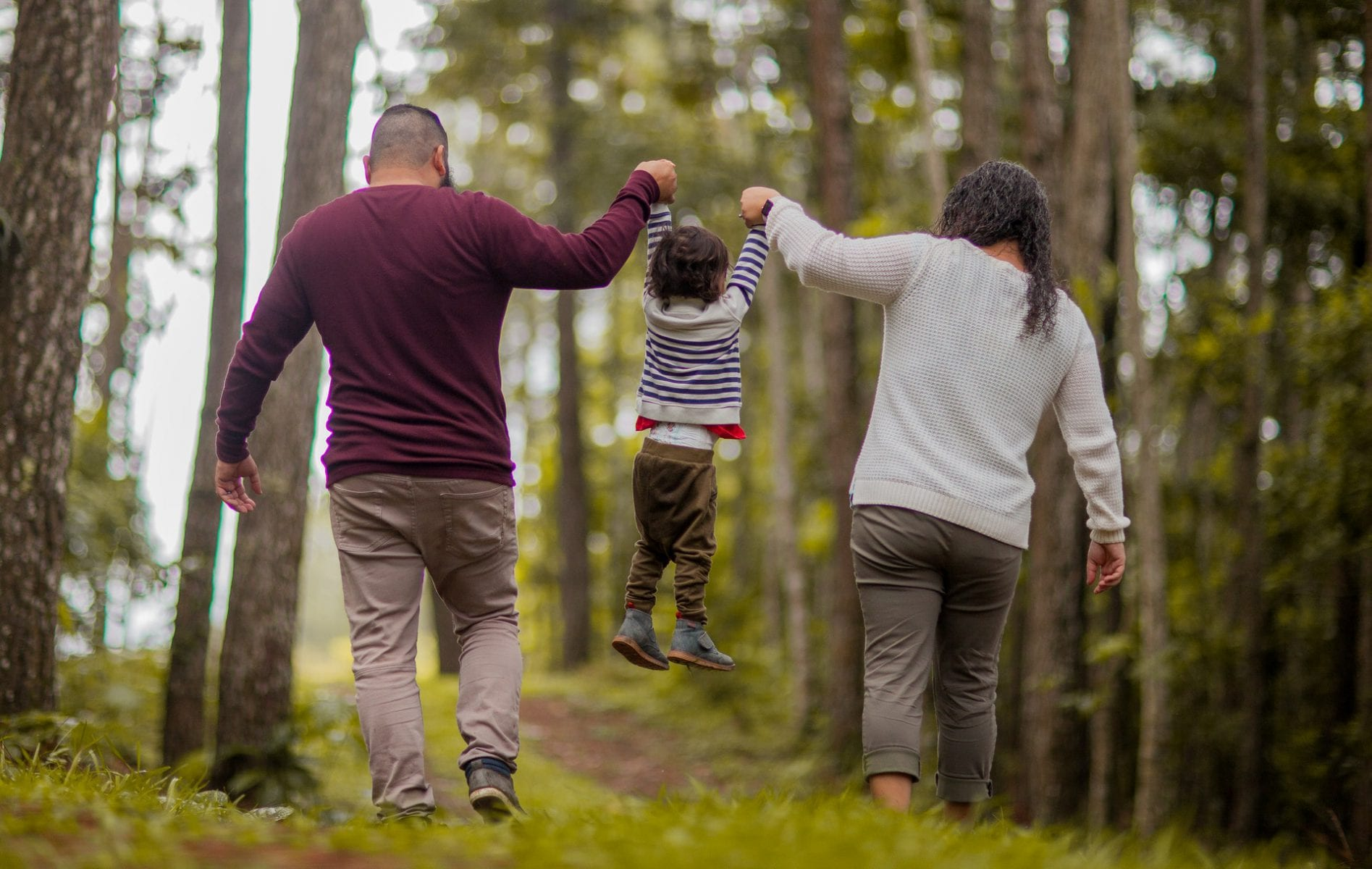 Mother and father carrying child in forest